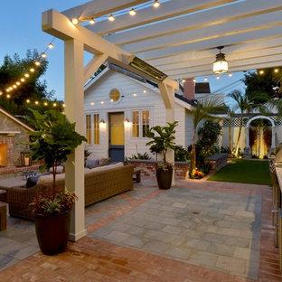 Foto di un piccolo patio o portico stile marino dietro casa con pavimentazioni in mattoni e una pergola