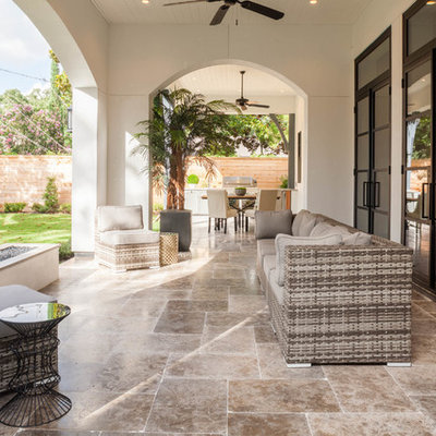 Example of a transitional backyard tile patio design in Houston with a fire pit and a roof extension