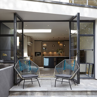 Inspiration for a contemporary back patio in London with concrete paving and no cover.