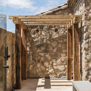 Idee per un patio o portico country di medie dimensioni e dietro casa con piastrelle e una pergola