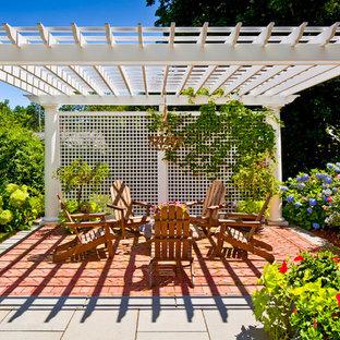 Foto di un patio o portico classico con pavimentazioni in mattoni e un gazebo o capanno