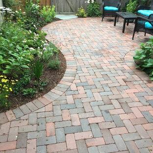 Idee per un patio o portico tradizionale di medie dimensioni e dietro casa con pavimentazioni in mattoni e nessuna copertura