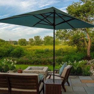 Diseño de patio de estilo de casa de campo, de tamaño medio, sin cubierta, en patio trasero, con brasero y adoquines de piedra natural