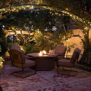 Esempio di un patio o portico tradizionale di medie dimensioni e in cortile con un focolare, pavimentazioni in mattoni e nessuna copertura