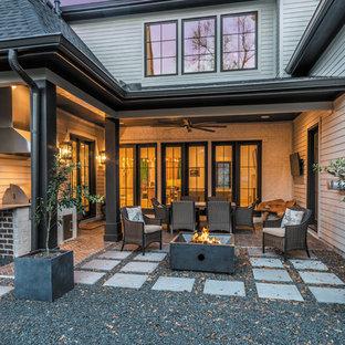 Esempio di un grande patio o portico moderno dietro casa con un focolare, un tetto a sbalzo e graniglia di granito