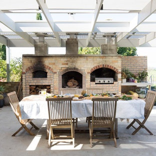 This is an example of a large country patio in Wollongong with an outdoor kitchen, concrete slab and a pergola.