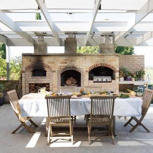 Foto di un grande patio o portico country con lastre di cemento e una pergola