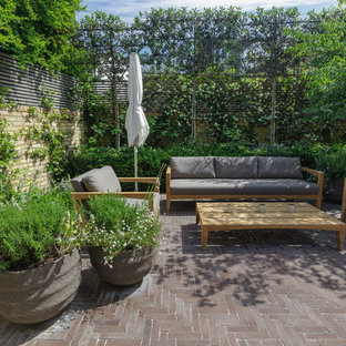 Small classic back patio in London with brick paving and no cover.