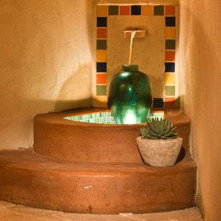 Esempio di un ampio patio o portico boho chic dietro casa con pavimentazioni in pietra naturale e una pergola