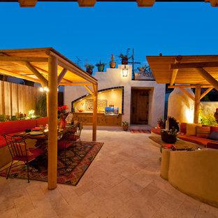 Ispirazione per un ampio patio o portico bohémian dietro casa con pavimentazioni in pietra naturale e una pergola
