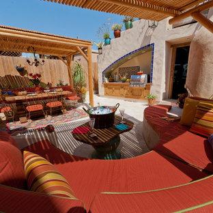 Idee per un ampio patio o portico eclettico dietro casa con pavimentazioni in pietra naturale e una pergola