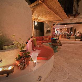Immagine di un ampio patio o portico bohémian dietro casa con pavimentazioni in pietra naturale e una pergola