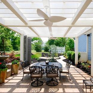 Cette image montre une terrasse traditionnelle de taille moyenne avec une pergola, un point d'eau et des pavés en brique.