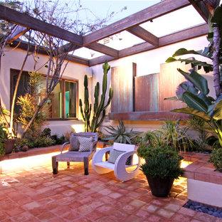 Island style patio photo in Orange County with a pergola