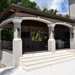 This is an example of a medium sized mediterranean back patio in Tampa with an outdoor kitchen, natural stone paving and a gazebo.