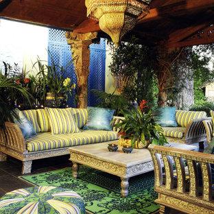 Idee per un patio o portico tropicale di medie dimensioni e dietro casa con piastrelle e un tetto a sbalzo