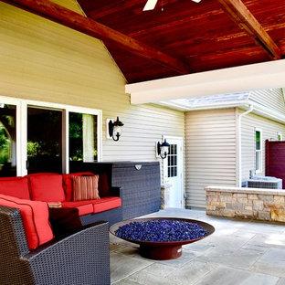 Ispirazione per un grande patio o portico stile americano dietro casa con un focolare, cemento stampato e un tetto a sbalzo