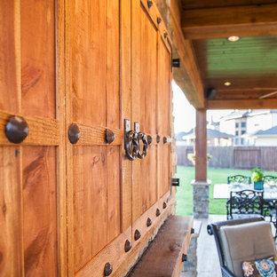 Ispirazione per un patio o portico rustico di medie dimensioni e dietro casa con cemento stampato e un tetto a sbalzo