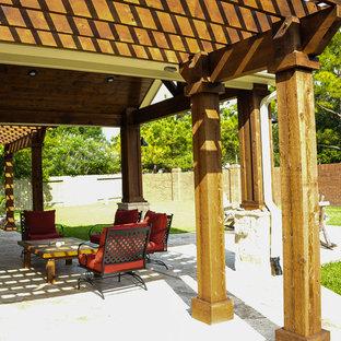Foto di un patio o portico tradizionale di medie dimensioni e dietro casa con un focolare, cemento stampato e una pergola