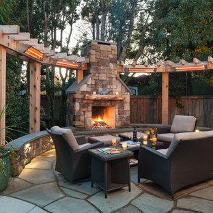 Unbedeckter Rustikaler Patio hinter dem Haus mit Natursteinplatten und Kamin in Seattle