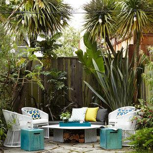 Ispirazione per un patio o portico tropicale dietro casa e di medie dimensioni con pavimentazioni in cemento, un focolare e nessuna copertura