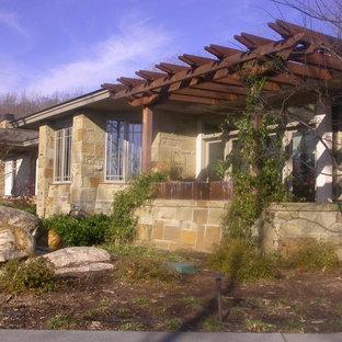 Idee per un ampio patio o portico american style davanti casa con pavimentazioni in pietra naturale e una pergola