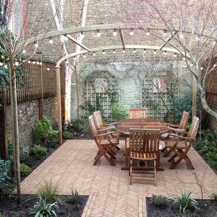Ispirazione per un patio o portico chic di medie dimensioni e dietro casa con pavimentazioni in mattoni