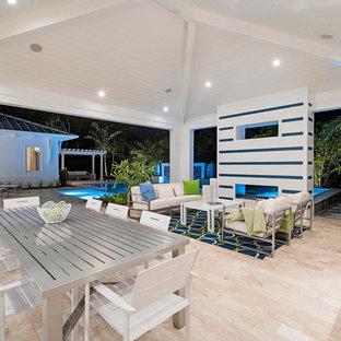 Immagine di un grande patio o portico chic dietro casa con piastrelle e un tetto a sbalzo