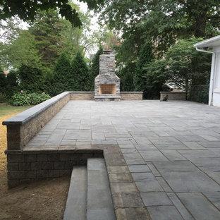 Ispirazione per un patio o portico american style di medie dimensioni e dietro casa con cemento stampato, nessuna copertura e un focolare
