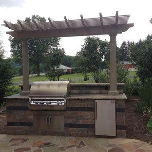 Idee per un grande patio o portico stile americano dietro casa con pavimentazioni in mattoni e una pergola