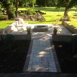 Esempio di un patio o portico american style di medie dimensioni e dietro casa con un focolare, cemento stampato e nessuna copertura
