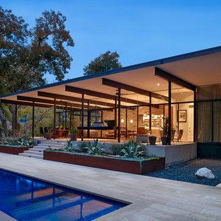 Foto di un grande patio o portico moderno dietro casa con pavimentazioni in pietra naturale e un tetto a sbalzo