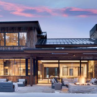 Ispirazione per un patio o portico rustico dietro casa con un focolare, pavimentazioni in cemento e un tetto a sbalzo