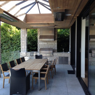 Inspiration for a large contemporary backyard concrete paver patio kitchen remodel in Vancouver with a roof extension