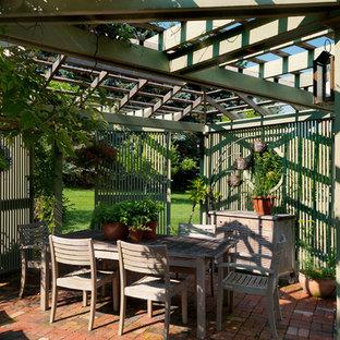 Immagine di un patio o portico country in cortile con una pergola