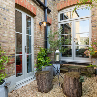 This is an example of a small scandi patio in London with gravel and no cover.