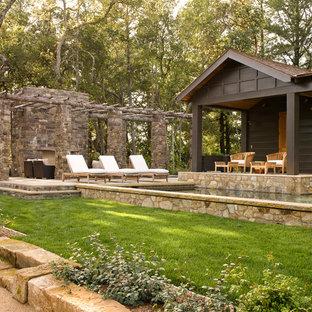 Esempio di un patio o portico stile rurale con un focolare e una pergola