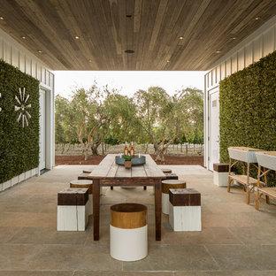 Ispirazione per un patio o portico country in cortile con piastrelle e un tetto a sbalzo