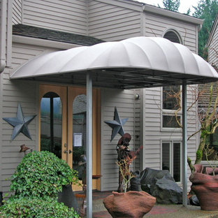 This is an example of a small traditional front patio in Portland with gravel and an awning.