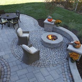 Immagine di un patio o portico classico dietro casa e di medie dimensioni con un focolare, pavimentazioni in cemento e nessuna copertura