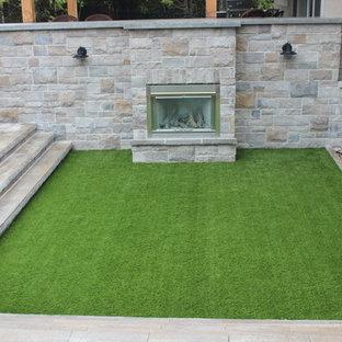 Ispirazione per un grande patio o portico contemporaneo dietro casa con un focolare, cemento stampato e una pergola
