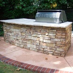 Idee per un patio o portico stile americano dietro casa con pavimentazioni in mattoni e nessuna copertura