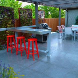 Immagine di un patio o portico moderno dietro casa con cemento stampato e una pergola
