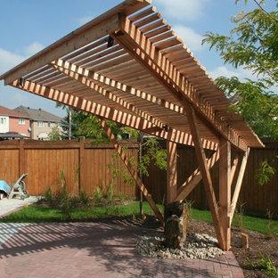 Cette photo montre une petite terrasse arrière chic avec une pergola et des pavés en brique.