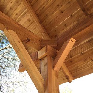 Immagine di un patio o portico american style di medie dimensioni e dietro casa con cemento stampato e un gazebo o capanno