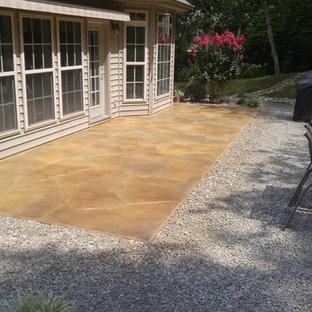 Esempio di un patio o portico chic di medie dimensioni e dietro casa con cemento stampato e nessuna copertura