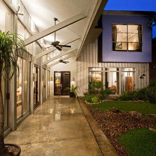 Exemple d'une terrasse arrière tendance de taille moyenne avec un auvent et une dalle de béton.