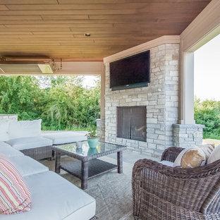 Esempio di un patio o portico american style di medie dimensioni e dietro casa con un focolare, pavimentazioni in pietra naturale e nessuna copertura