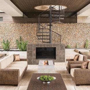 Idee per un ampio patio o portico minimal dietro casa con un focolare e un tetto a sbalzo