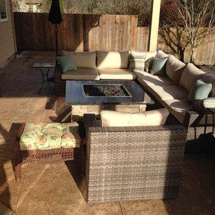 Foto di un patio o portico american style di medie dimensioni e dietro casa con un focolare, cemento stampato e un tetto a sbalzo